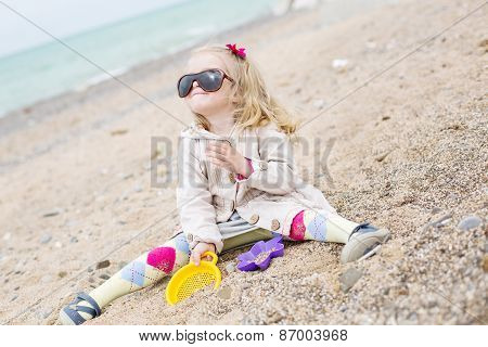 Happy Cute Little Girl Playing On The Beach