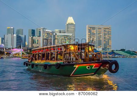 Colorful riverboat cruises in the harbor at sunset in Singapore