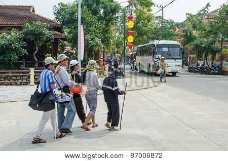 Blind men and women holding onto to each other while walking together across the street  in Vietnam