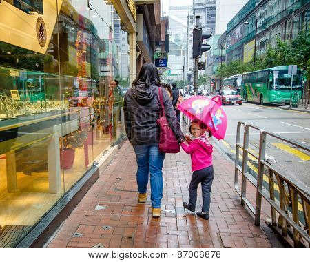 A little girl with a pink umbrella walks along the street in Hong Kong with her mother in the rain