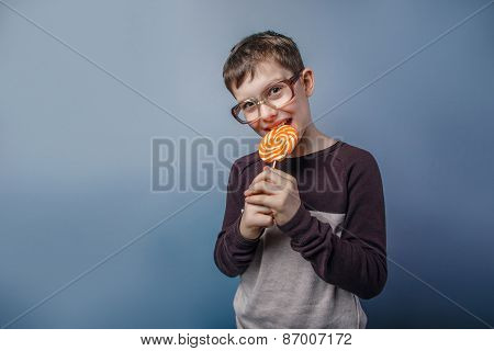 European-looking boy of ten years in glasses, chewing candy in h