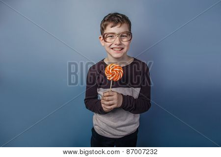 European-looking  boy of ten years in  glasses licking a lollipo