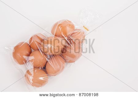 Eggs In A Plastic Bag On White Paper Background