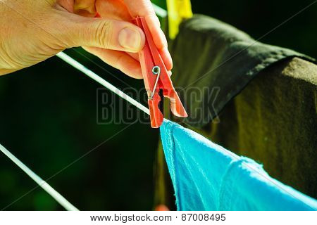 Woman Hand Hanging Wet Clothes On Rope Line