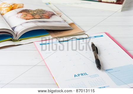 A Calendar And Stack Of Cookbooks