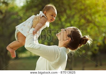 Mother Lifting Up And Turning Around Little Baby Daughter In Park