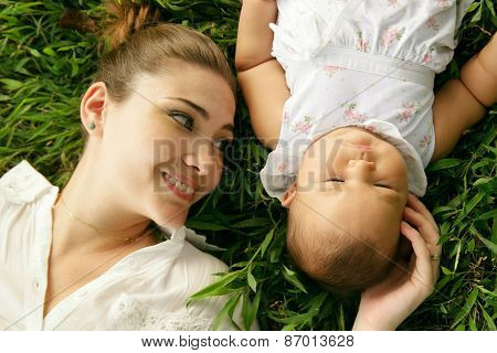 Mother With Little Baby Daughter Laying On Grass