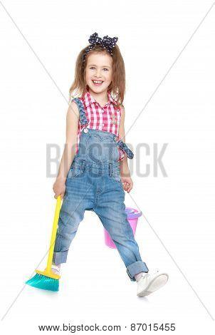 funny little girl in denim overalls sweeping the floor