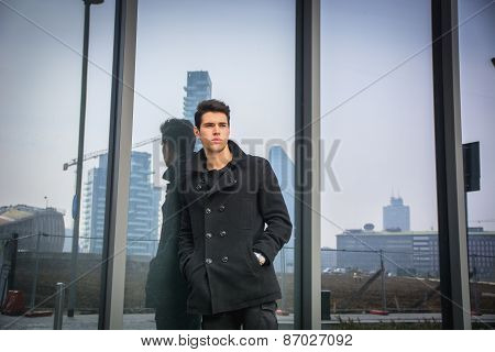 Stylish trendy young man standing outdoor against office window