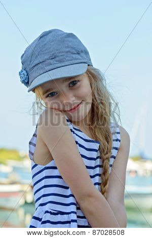 Portrait of little girl in denim cap outdoors