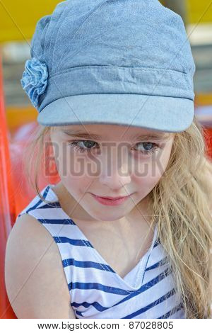 Portrait of small girl in striped clothes outdoors