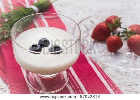 Yogurt with blackberry, strawberry on background