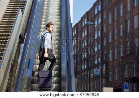 Young Man Walking Up Escalator With Travel Bags