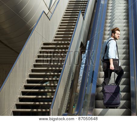 Handsome Man Walking Up Escalator With Travel Bags
