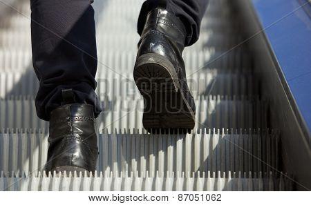 Male Feet Walking In Boots Up Escalator