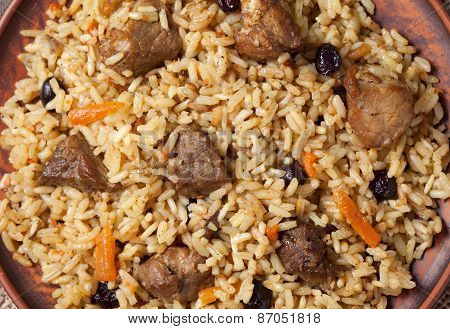 Pilaf with large pieces of fried meat, spicy rice, carrot and raisins. Close-up shot, top view.