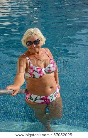 Aged Woman Is Posing In Pool Water Near Handrails.