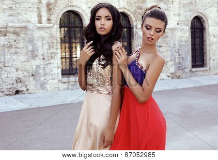 Photo Of Two Beautiful Girls With Dark Hair In Luxurious Dresses