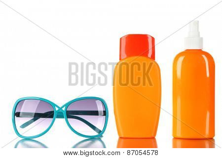 Bottles of suntan cream with sunglasses isolated on white