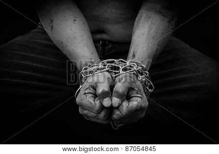 Hands of a man who was imprisoned by the chain.