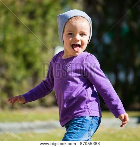 lovely young girl posing and laughing with cap at spring