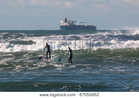 Men Paddleboarding On Board In The Waves, Supply Ship In Background