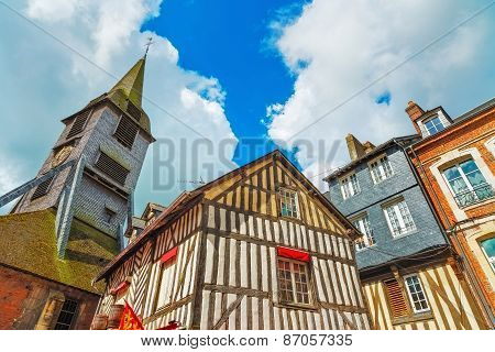Old Wooden Facades And Church In Honfleur Normandy, France.