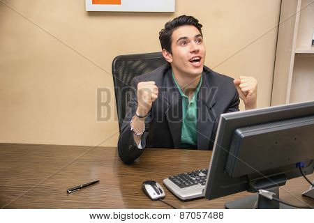 Happy young businessman screaming for joy, at desk in office