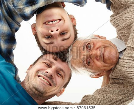 Grandfather, Father And Son Looking Down Into Camera