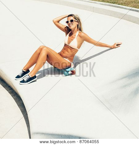 Beautiful Young Woman Sitting On Longboard In Sunny Day
