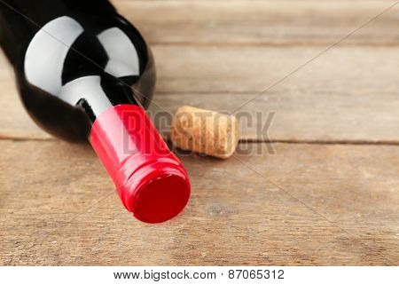 Glass bottle of wine with cork on wooden table background