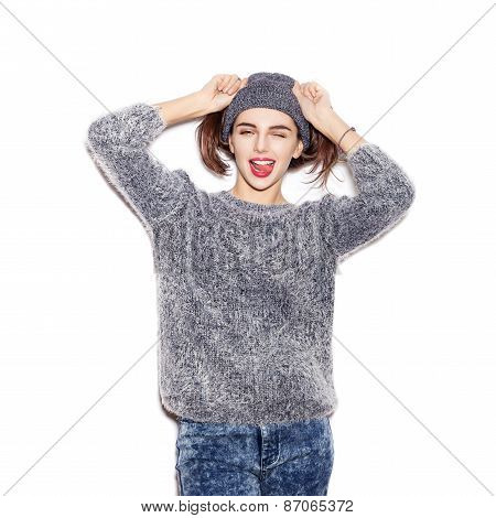 Funky Girl In Knit Sweater And Hat Winking And Showing Tongue