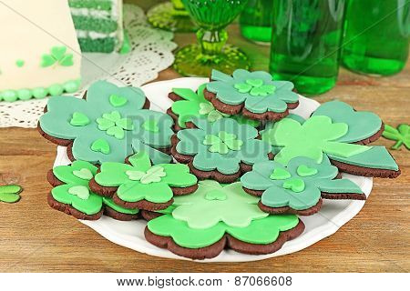 Still life with sliced cake, cookies and green beer for Saint Patrick's Day on wooden table background