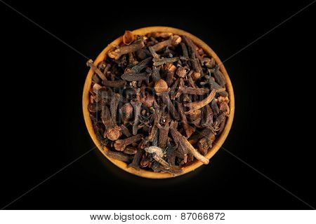 Clove spice in wooden bowl, isolated on black