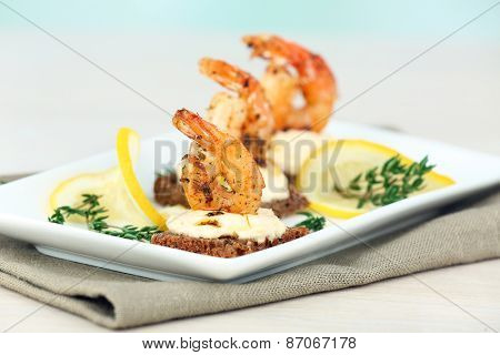 Appetizer canape with shrimp and lemon on table on light background