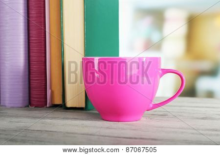Color cup of drink with books on wooden surface and light background
