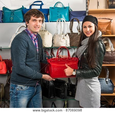 Shop Assistant Showing Red Leather Bag To Beautiful Girl