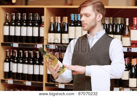 Sommelier in the store near shelves