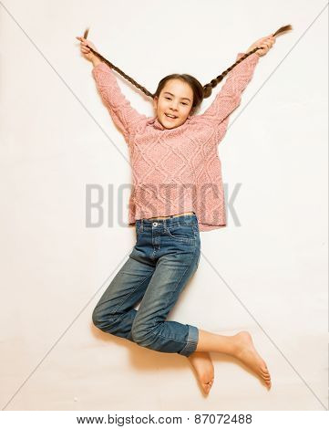 Isolated Shot Of Happy Girl With Long Braids Jumping Up High