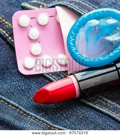 Closeup oral contraceptive pills, condom and red lipstick in denim pocket.