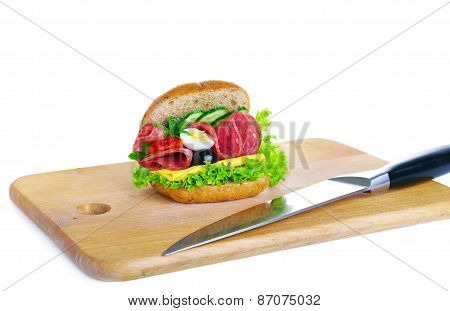 Fresh Sandwich And A Knife Lying On A Wooden Board