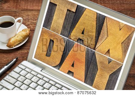 tax day in letterpress wood type - a message on a laptop screen with cup of coffee