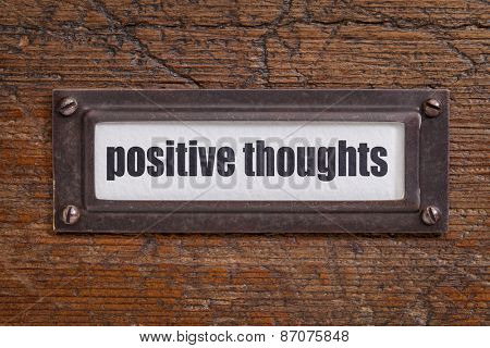positive thoughts  - file cabinet label, bronze holder against grunge and scratched wood