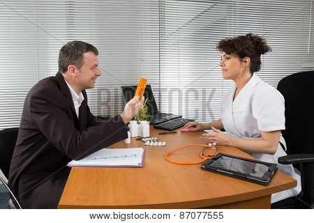 Businessman With Female Doctor At Her Office
