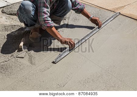 Construction Worker Spreading Wet Concrete