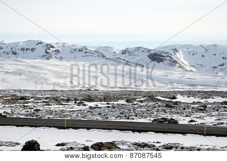 Electric cables and pylon towers on the snow covered land and mountains during winter