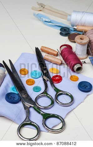 Sewing kit with scissors buttonsspools of thread and needles on white wooden background.