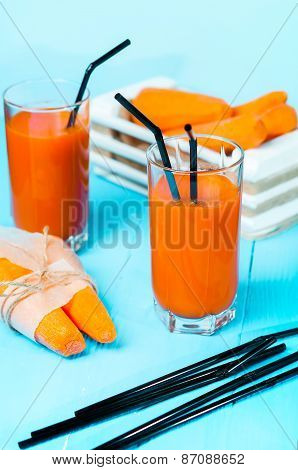 Freshly squeezed carrot juice in the glasses.A box with purified carrot on a blue wooden background.