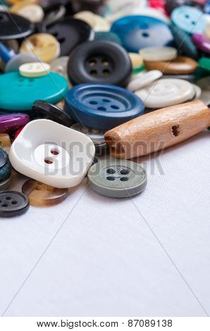 Old colored buttons for background on white fabric