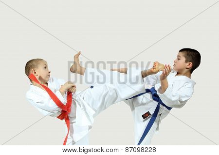 Two boys in karategi are beating blows kicks